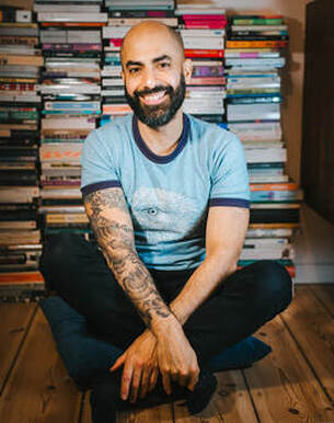 JPSinghphotography sits on a wooden floor in front of piles of books in black trousers and blue shirt